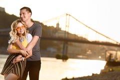 Boyfriend hugging girlfriend on river beach. During sunset royalty free stock image