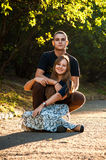 Boyfriend hugging girlfriend which sitting on the road in the park. Happy young couple having fun in the park royalty free stock image