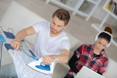 Boyfriend ironing while girlfriend relaxing on sofa Stock Image