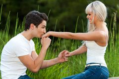 Boyfriend kissing girls hand outdoors. Stock Photo
