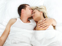 Boyfriend kissing her girlfriend in bed. High view of boyfriend kissing her girlfriend in bed Royalty Free Stock Photography