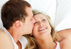 Boyfriend kissing his girlfriend in bed Stock Photo