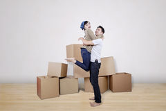 Boyfriend lift girlfriend at new home. Surrounded with boxes Royalty Free Stock Photography