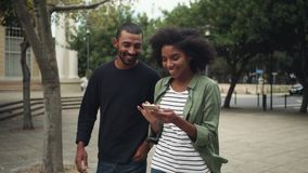 Boyfriend looking at girlfriend`s mobile phone while walking on street. Smiling african young woman with smart phones walking with her boyfriend on street stock video footage