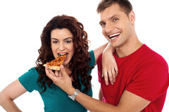 Boyfriend making her girl eat hot pizza piece Royalty Free Stock Photos