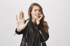 Boyfriend mocking girl with huge spider. Frightened and shocked woman pulling palm in no or stop gesture towards camera. Biting fingernail from fear, frowning Stock Photography