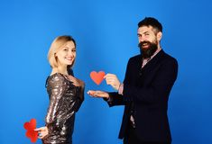 Boyfriend offers his love to girlfriend. Love symbol and dating. Concept. Girl and bearded men with happy faces share paper heart cards for valentines. Couple royalty free stock photos