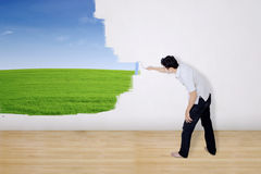 Boyfriend painting green field on wall Royalty Free Stock Photography