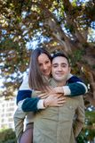 Boyfriend plays with his girlfriend carrying her up her back in a public park royalty free stock photos