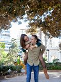 Boyfriend plays with his girlfriend carrying her up her back in a public park royalty free stock images