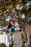 Boyfriend plays with his girlfriend carrying her up her back in a public park stock image