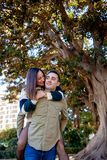 Boyfriend plays with his girlfriend carrying her up her back in a public park stock images