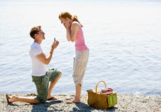 Boyfriend proposing to girlfriend. Near stream Stock Image