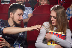Boyfriend pulling hand to popcorn of his greed girlfriend. Royalty Free Stock Images