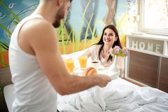 Boyfriend serving breakfast in bed to girlfriend. Boyfriend with love serving breakfast in bed to girlfriend Royalty Free Stock Images