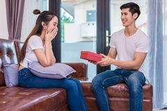 Boyfriend surprising girlfriend with present. Woman surprised when looking at gift box on special day. Lovers and Couples concept. Honeymoon and Dating theme stock image
