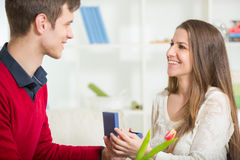 Boyfriend surprising his girlfriend with gift, in the living room. Stock Images