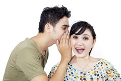Boyfriend tell secret to girlfriend - isolated. Boyfriend tell secret to girlfriend on white background royalty free stock photography