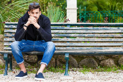 Boyfriend waiting. Handsome young man model sitting on the bench. A handsome young man is sitting on a bench watching and waiting. The boy wearing trendy clothes Royalty Free Stock Images