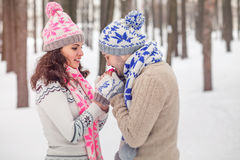 Boyfriend warms hands girlfriend, frozen in the cold winter park Royalty Free Stock Images