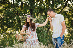 Boyfriend in white shirt and jeans shorts kissing hand her girlfriend, wearing dress in floral print and flower wreath holding bas Stock Photos