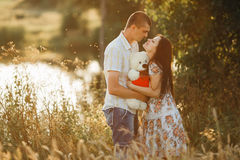 Boyfriend in white shirt and jeans shorts kissing hand her girlfriend, wearing dress in floral print and flower wreath holding bas Royalty Free Stock Images