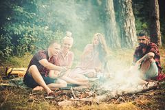 Boyfriends and girlfriends enjoy camping food. Friends have picnic at bonfire in forest. Men and women roast sausages on stock images