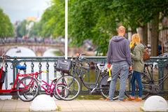 Boyfriends observe the canals of Amsterdam from a bridge.  royalty free stock image