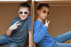 Boyfriends sitting in paper box Royalty Free Stock Photo
