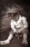 Boyhood Charm. Little barefoot boy looking down at box turtle, old fashioned clothes stock images