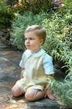 Boyhood in the Garden. Young boy kneels on a garden path.  He has on a yellow suit with short sleeves.  He has a pensive thoughtful look on his face Stock Image