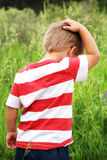 Boyhood Sense of Wonder. A young boy explores the great outdoors while creating some thoughts in this candid image of him scratching his head during his boyhood Stock Image