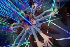 Boyl sits stretching arms at crossing in mirror labyrinth. Boyl sits stretching his arms at crossing in mirror labyrinth illuminated with color lights royalty free stock photos