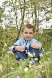 The boyl in the woods sitting near the flowers. Royalty Free Stock Photo