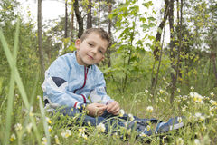 The boyl in the woods sitting near the flowers. Stock Photo