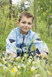 The boyl in the woods sitting near the flowers. Royalty Free Stock Photos