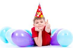 Boylying de sourire heureux sur le plancher avec les ballons colorés Photos libres de droits