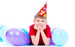 Boylying de sourire heureux sur le plancher avec les ballons colorés Photographie stock
