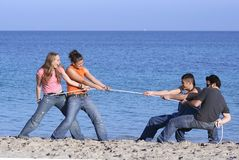 Boys against girls. Two boys having tug of war with two girls on beach Royalty Free Stock Photography