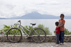 Boys aside a leftover bike. PANAJACHEL, GUATEMALA - SEPTEMBER 14, 2013: Two brothers poses aside a leftover bike next to the shores of Lake Atitlan. September 14 Stock Images