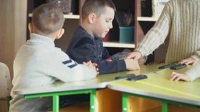 Boys assemble designer. The boys assemble the designer at the school desk stock video