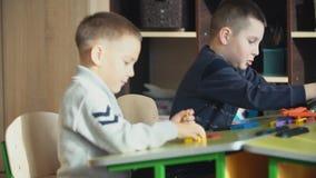Boys assemble designer. The boys assemble the designer at the school desk stock video footage