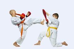 Boys athletes are beating kick mae-geri on simulators Royalty Free Stock Images