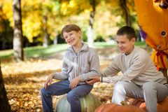 Boys in the autumn park. Two boys sitting on a big pumpkin in the autumn park Royalty Free Stock Photography
