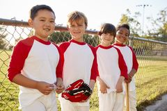 Boys in a baseball team with mitt and bat looking to camera stock photography