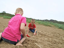 Boys at the beach. Brothers playing in the sand on a beach Royalty Free Stock Photo