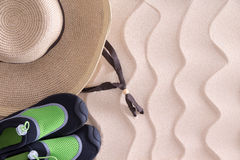 Boys beach hat and shoes on golden sand Royalty Free Stock Photography