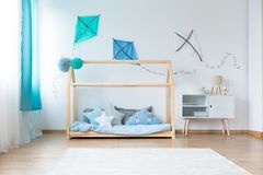 Boys bedroom with DIY kites. Small lamp on cupboard next to bed with star shaped pillows on blue bedding in boys bedroom with DIY kites on white wall stock images