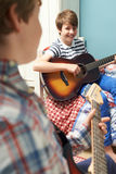 Boys In Bedroom Playing Guitars Together Royalty Free Stock Photo
