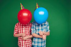 Boys behind balloons Stock Images